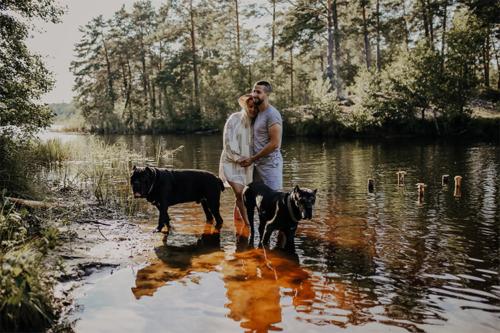 divi cilvēki un divi suņi upes krastā