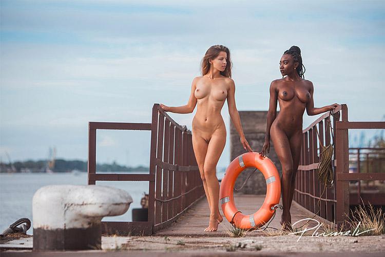 divas meitenes kailas fotgrāfējas ostā