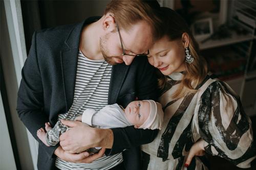 jaundzimušais tēva rokās bauda mātes smaidu