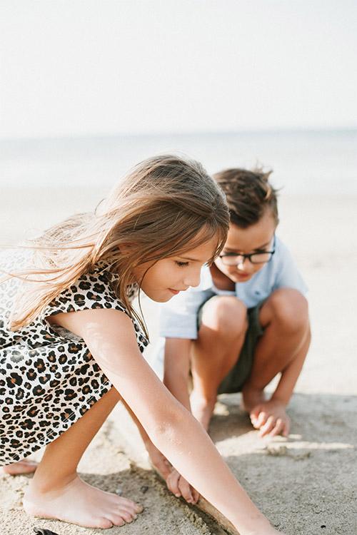 bērni kaut ko zīmē jūras smiltīs
