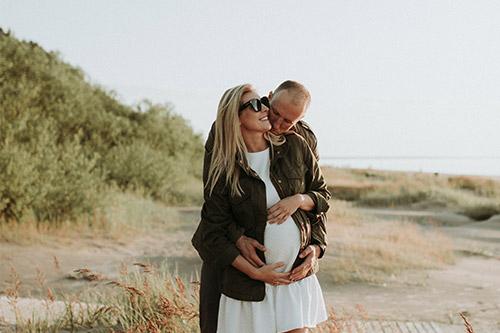 gaidībās esoša ģimene priecājas jūras krastā