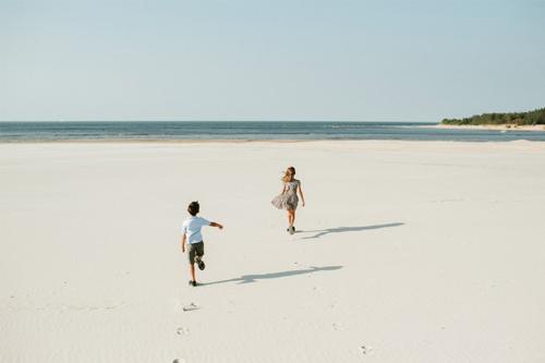 bērni skrien uz Gaujas ieteku jūrā