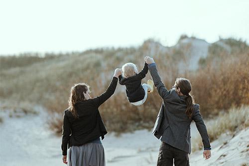 mamma un tētis paceļ bērnu virs savām galvām