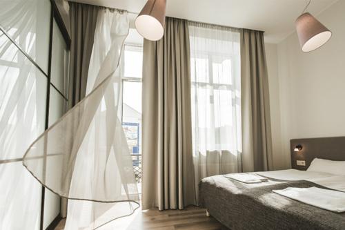 gaišs guļamistabas interjers ar plīvojošiem aizskariem