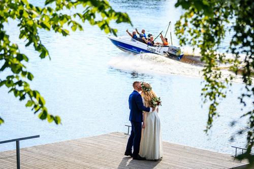 līgava un līgavainis uz terases pie ūdens