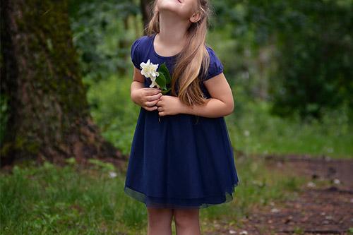 smaidīga meitenīte ar puķi rokās