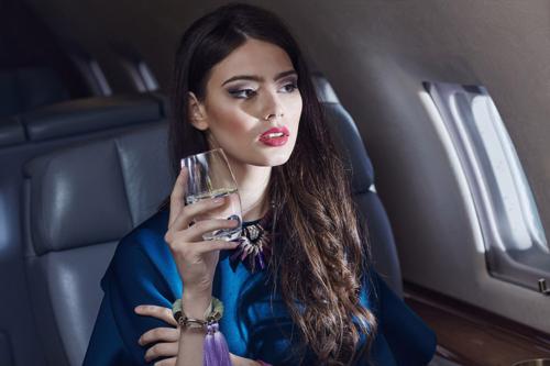 skaista sieviete lidmašīnas salonā ar glāzi ūdens