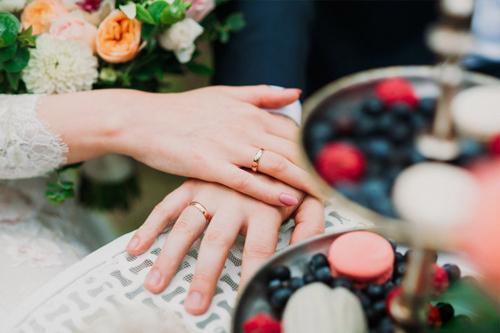 jaunlaulāto rokas viena uz otras, uzvilktiem laulību gredzeniem