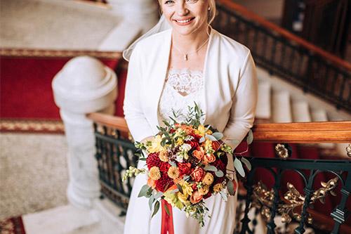 līgava ar skaistu pušķi rokās stāv uz kāpnēm