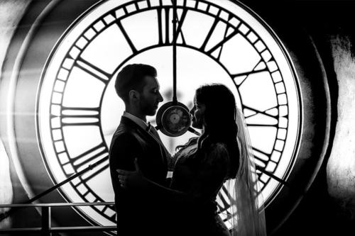 vīrs ar sievu pie baznīcas pulksteņa silueta