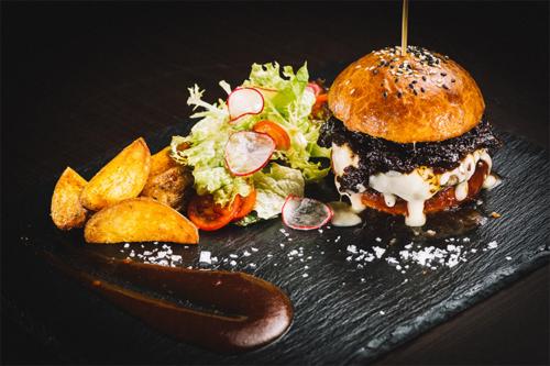 sulīgs burgers ar salātiem un kartupeļu daiviņām