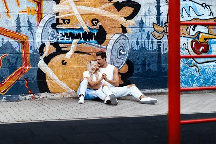 pāra fotosesija uz graffiti sienas fona